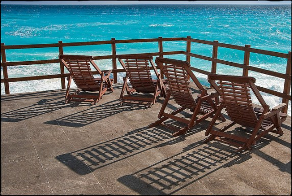 deck chairs on beach via flickr by mike mcholm
