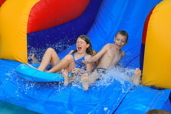 Kids on water slide by Steve Alexander via Flickr