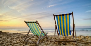 Two empty deck chairs on a beach at sunrise